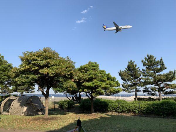 城南島海浜公園キャンプ場の真上を飛ぶ飛行機